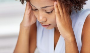 people, emotions, stress and health care concept - unhappy african american young woman touching her head and suffering from headache