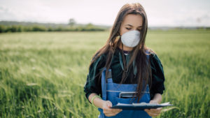 Female Extension agent with face covering holding a clipboard while standing in a green wheat field.