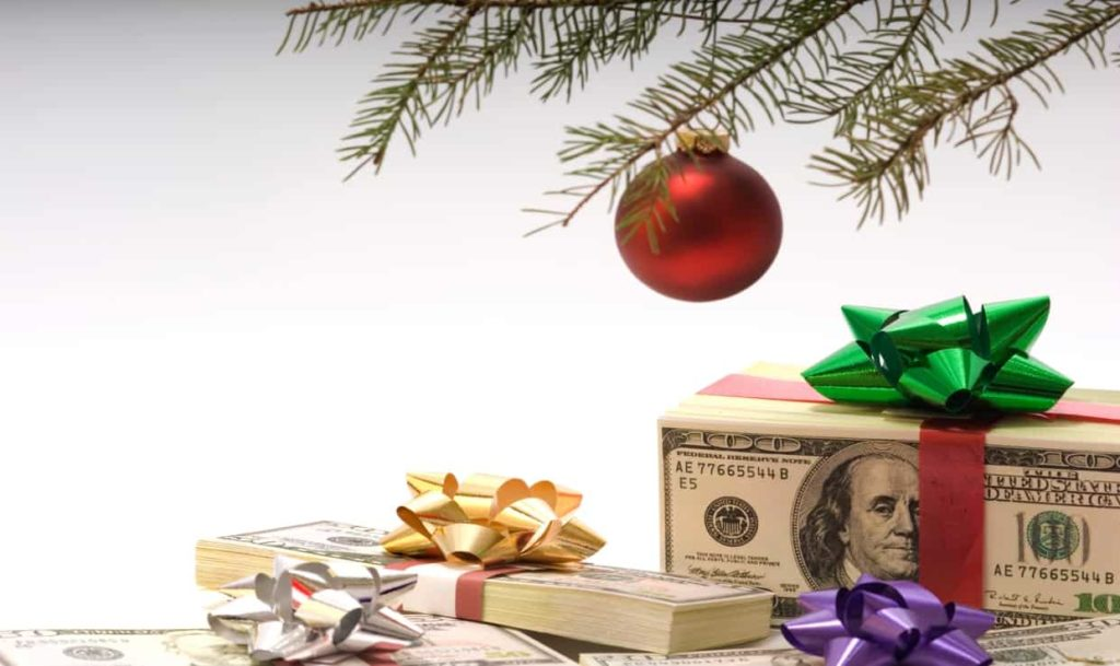 Holiday ornament on tree with money underneath